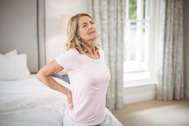 Woman that is sitting on her bed and experiencing back pain.