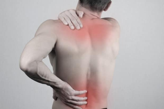 View of a man's back as he is holding areas in pain.