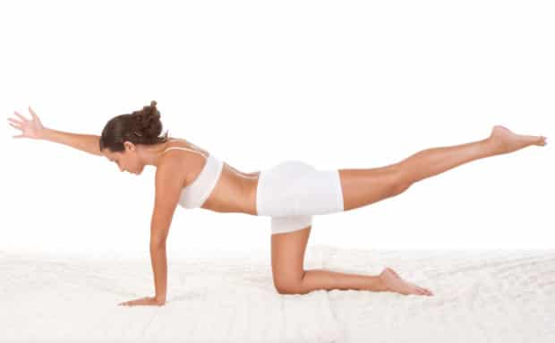 Woman that is doing a back workout to have a strong back, while she is in white workout clothes.