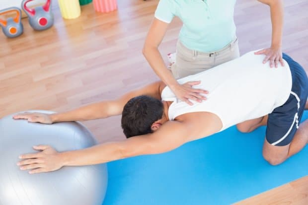 Man doing a back exercise with the help of a physical and chiropractic therapist.