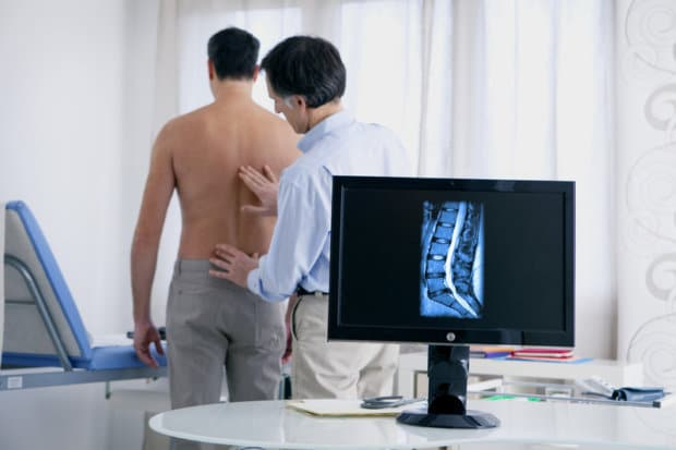 A shirtless patient in a medical office that is having his back examined. On the screen behind him, there is an x-ray image of a bulging disc in his back.