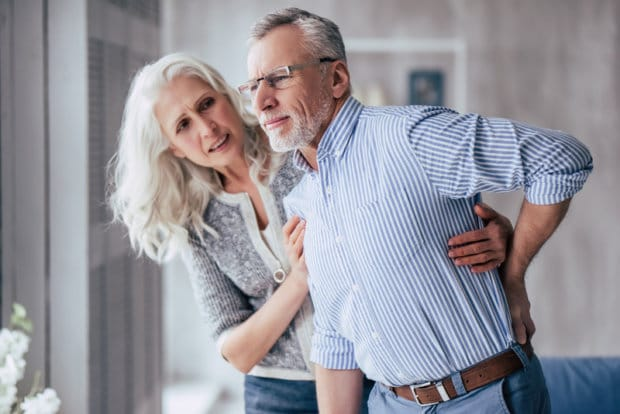 An elderly couple. The woman is helping the man to stand, as he is experiencing back pain that has him bending forward.