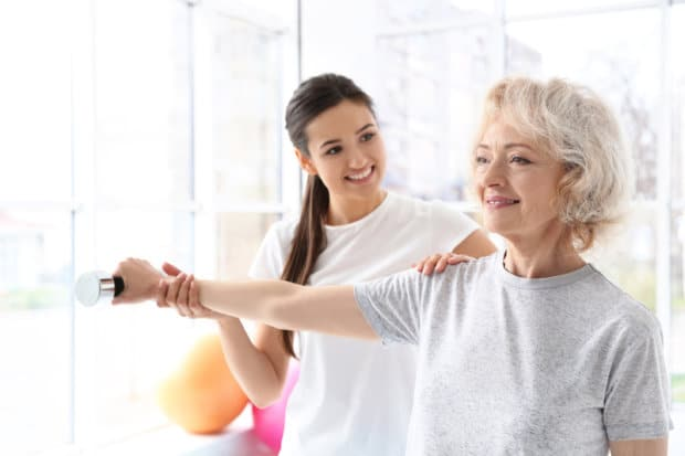 A beautiful elderly woman that is doing rehabilitative exercises with a trainer.