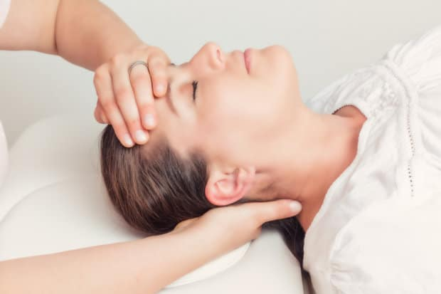 A close-up view of a patient with headache pain that is having a chiropractic adjustment on their head and neck.