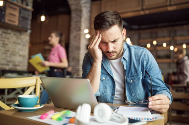 A man that is studying in a coffee-shop type of establishment. He is taking a minute away from his computer and studies to hold his head that is in pain.