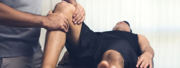 An active man that is having his knee examined by a physical therapist.