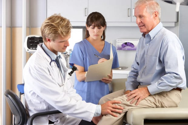 An elderly man that is having his knee examined by medical professionals.