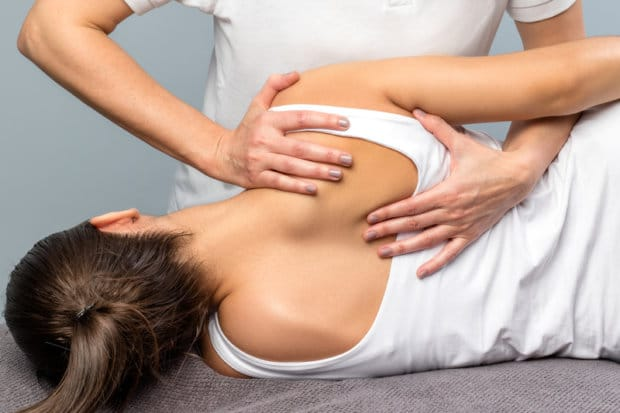A close-up view of a female patient having her back adjusted by a chiropractor.