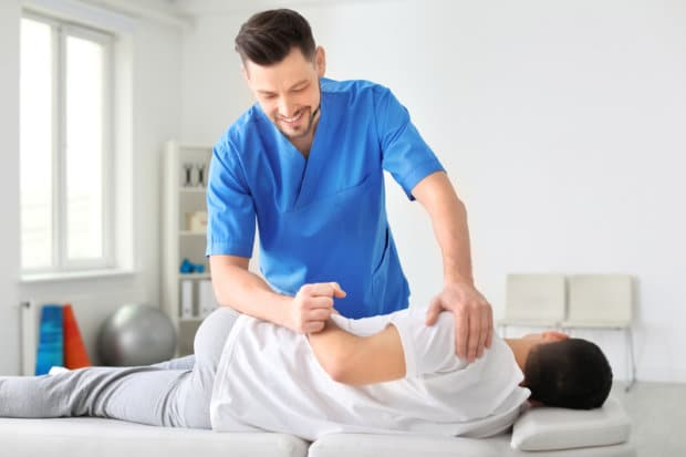A chiropractic professional that is adjusting a male patient's back.