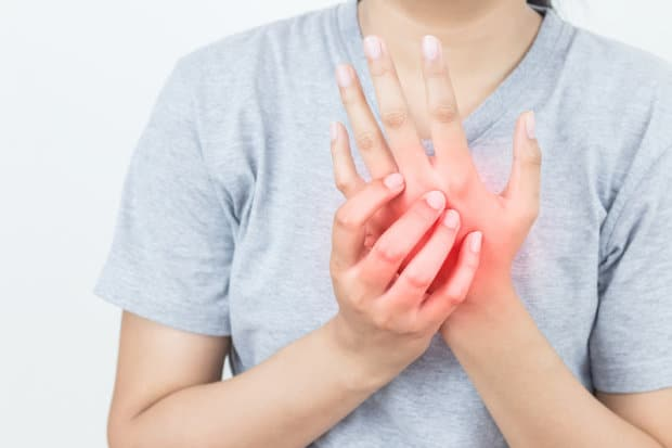 A close-up view of a woman that is holding her hand that is in pain from neuropathy. The area that is in pain is highlighted in red.