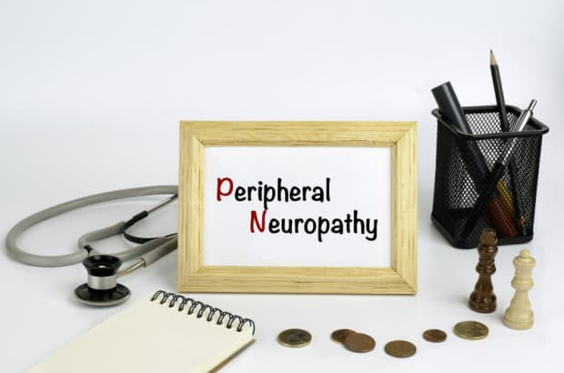 """A framed photo that says """"Peripheral Neuropathy"""" with items such as coins, a notepad, a stethoscope and other medical items surrounding the framed image."""